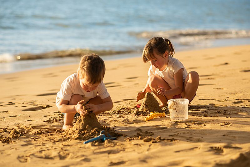 dzieci na plaży budują zamki