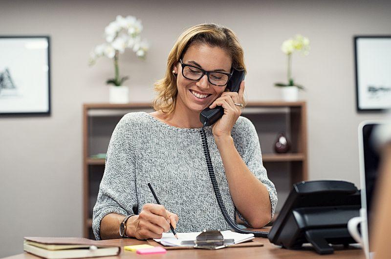 Ustalenie terminu rezerwacji noclegu kobieta rozmawia przez telefon