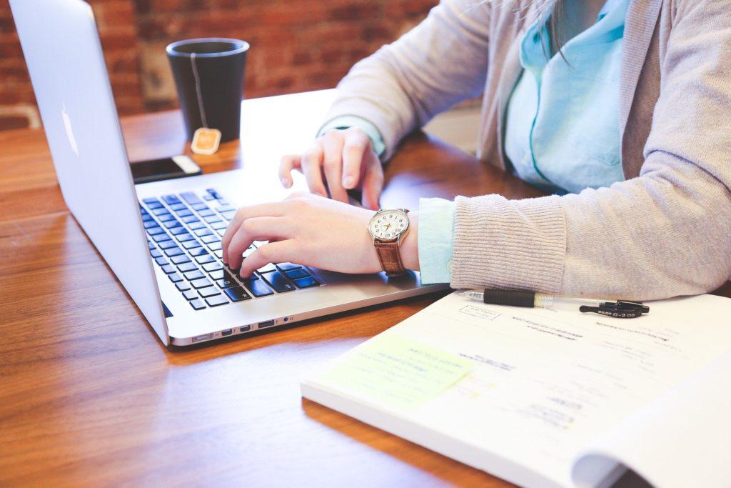 kobieta z laptopem na stole tworzy prezentację obiekt noclegowego