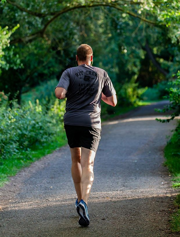 Biegacz, mężczyzna, biegnie po ścieżce leśnej